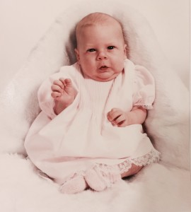 Jess at 1 month old. She is wearing a pink dress and booties and is laying on a pink fuzzy blanket. Her eyes seem to be looking right towards the camera.
