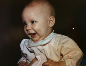 Baby Jess wearing a pink long-sleeve jumper. Jess is smiling and her eyes appear to be looking at the person who is holding her.