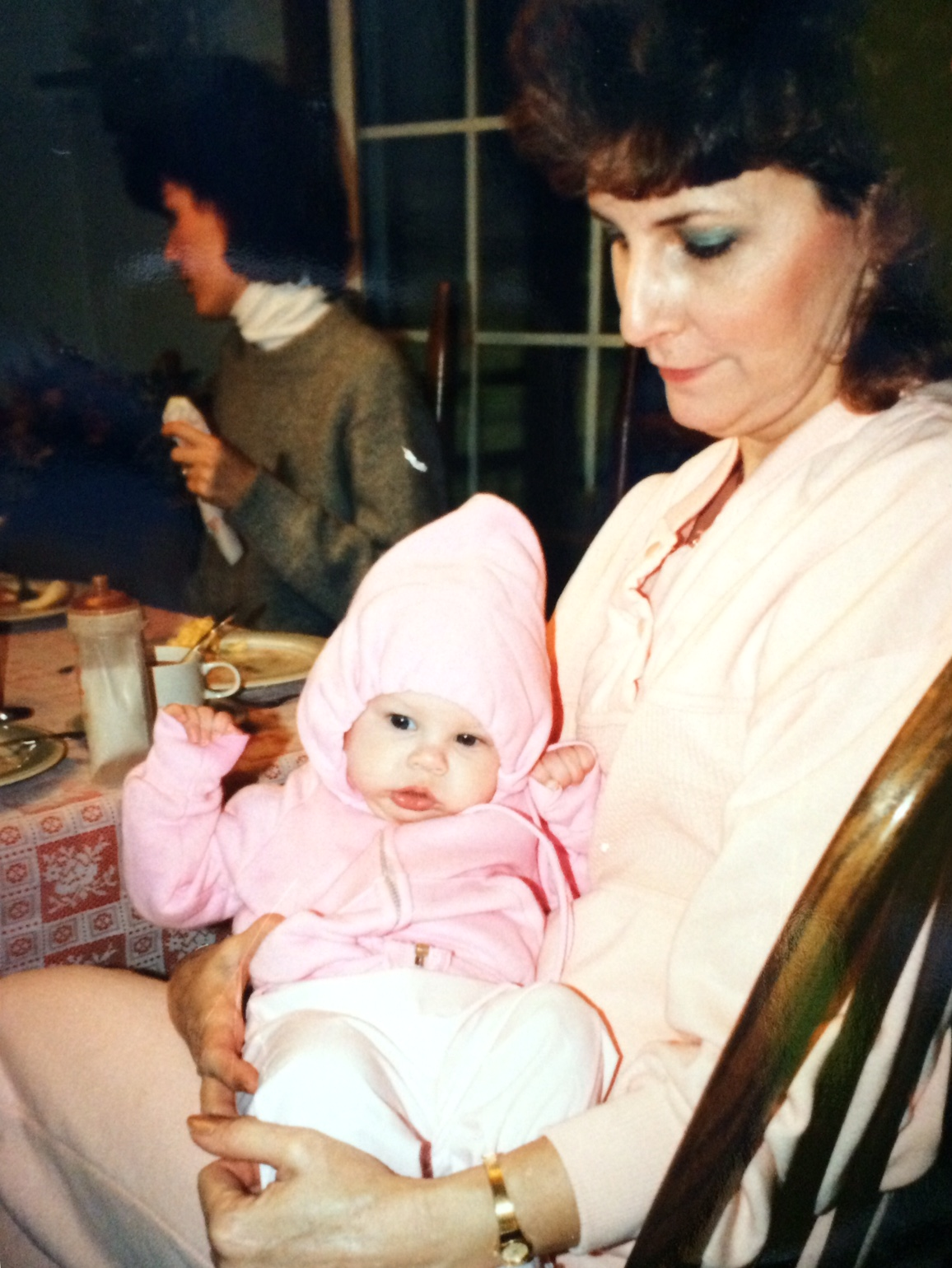 Sitting at the dining room table, Nonnie is holding a little Jess. Jess is wearing a light pink zip-up hoodie with the hat on her head and the drawstrings pulled snug.