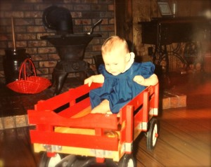 Jessica sitting in a red wagon