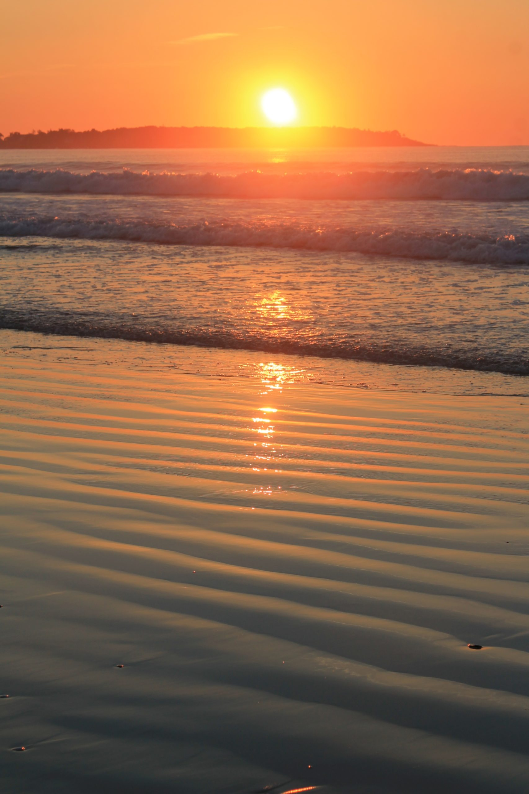 Sunset over gentle rolling waves on the ocean. She sun and sky look orange with no clouds to be seen.