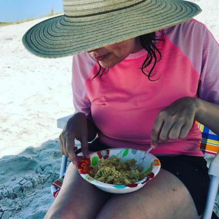 Jess on the beach eating a bowl of rice pilaf - a variety of foods that she will eat.