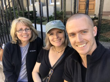 Val sitting on a bench with her son Madison and her friend Pam. They are io a bench in front of a black iron fence that surrounds a historical home in Charleston.