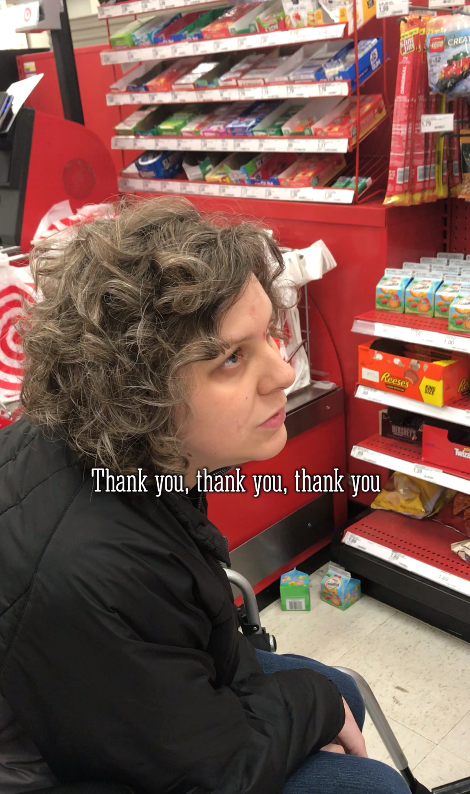 Jess in her wheelchair at the checkout line in Target. Jess is wearing a black coat.