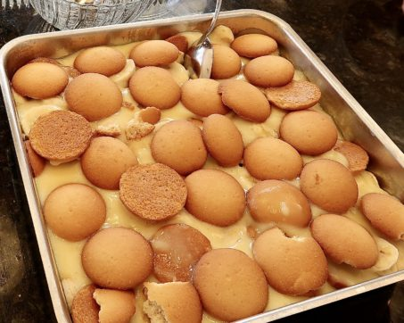An 9X9 metal pan with banana pudding in it. The top of the banana pudding is a layer of vanilla crackers