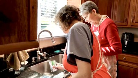 Jess and Nonnie standing at the kitchen sink. Nonnie is explaining to Jess how to empty a can of asparagus into a strainer.