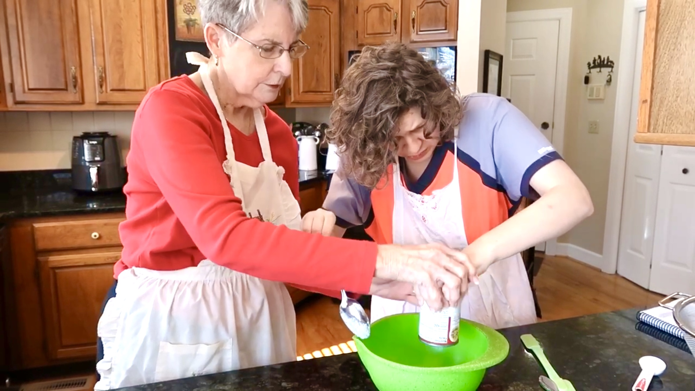 Jess and Nonnie are standing at the kitchen counter. Nonnie is assisting Jess, hand over hand, to get some condensed soup out of a can and into a green plastic bowl.