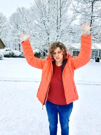 Jess standing out in snow. She's wearing an orange jacket, red shirt underneath, and bluejeans. She's not wearing a hat. She is holding both arms up, trying to feel of the snow falling.