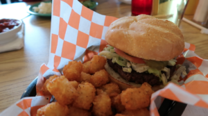 Hamburger and Tots in a basket lined with orange and white checkered paper