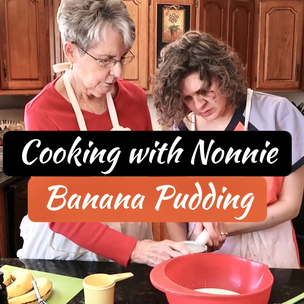 Nonnie and Jess are standing at the counter in Nonnie's kitchen. The counter is dark granite. Nonnie is wearing a red long-sleeve shirt and a white apron. Jess is wearing a scrub top with a white apron. Nonnie is helping Jess scoop out some cornstarch with a tablespoon. On the counter are bananas, vanilla wafers, a red bowl, and a spatula.