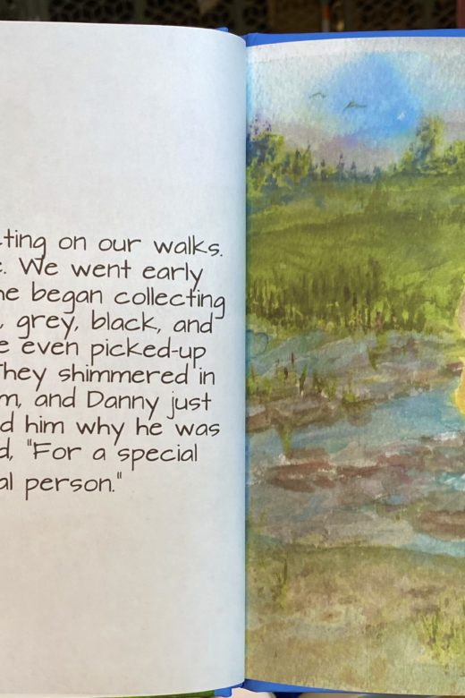 """""""Danny's Special Collection"""" opened up to a page. Writing is on the left page and a drawing on the right page. The text says """"One day Danny began collecting on our walks. This was a new adventure. We went out early one Saturday morning and he began collecting stones: large, rough stones, grey, black, and orange-speckled stones. He even picked-up lucky stones and pebbles. They shimmered in the sunlight in a small stream and Danny just kept picking them up. I asked him why he was collecting them and he said, """"For a special reason, for a special person."""""""" The drawing on the right page depicts a girl in a yellow dress and a boy in blue shorts and a brown shirt. They are standing in a shallow stream. Surrounding them are fields of green."""