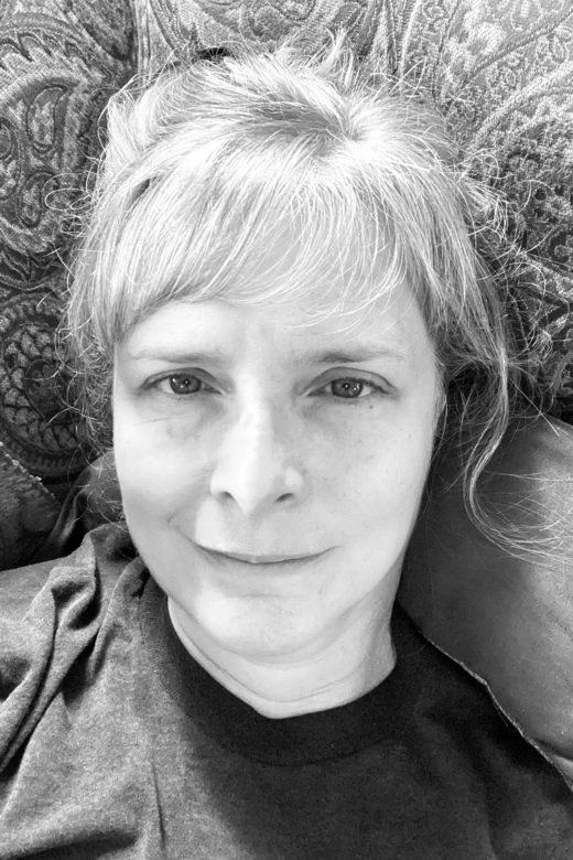 Black & White picture of Val - Reality - laying on couch, tired, hair up, no makeup