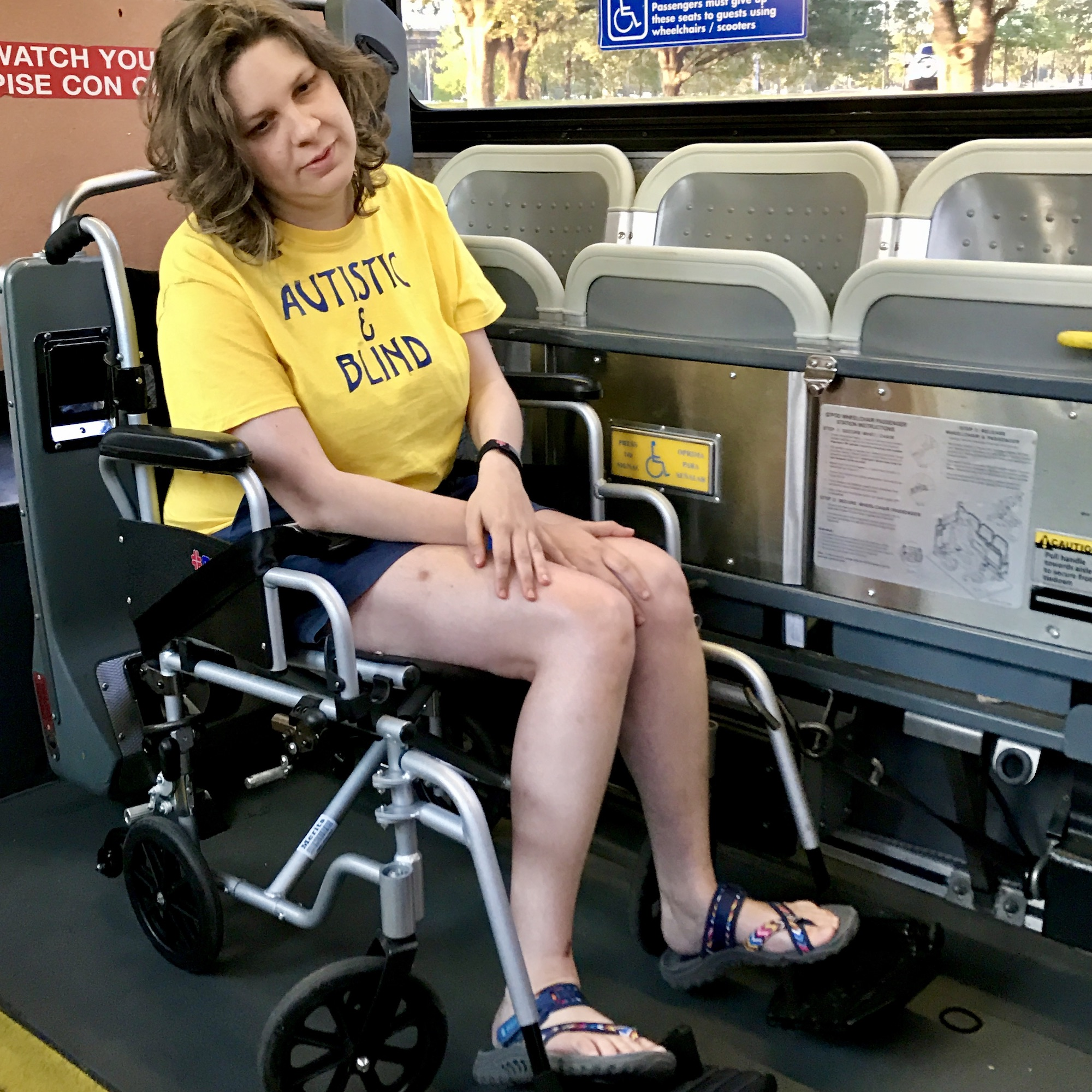 Jess is sitting in a wheelchair and the chair is strapped in on a bus.