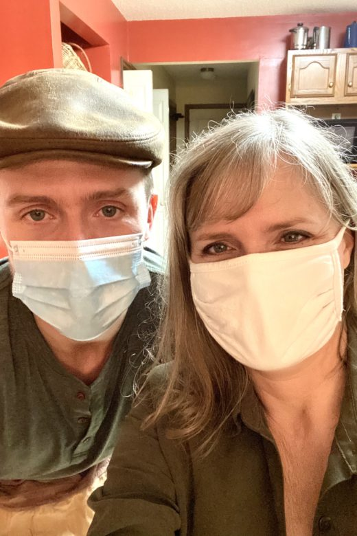 On the left, Madison, Val's son, wearing a green shirt, a cap and a medical face mask. Val on the right, wearing a green shirt and a cloth face mask.