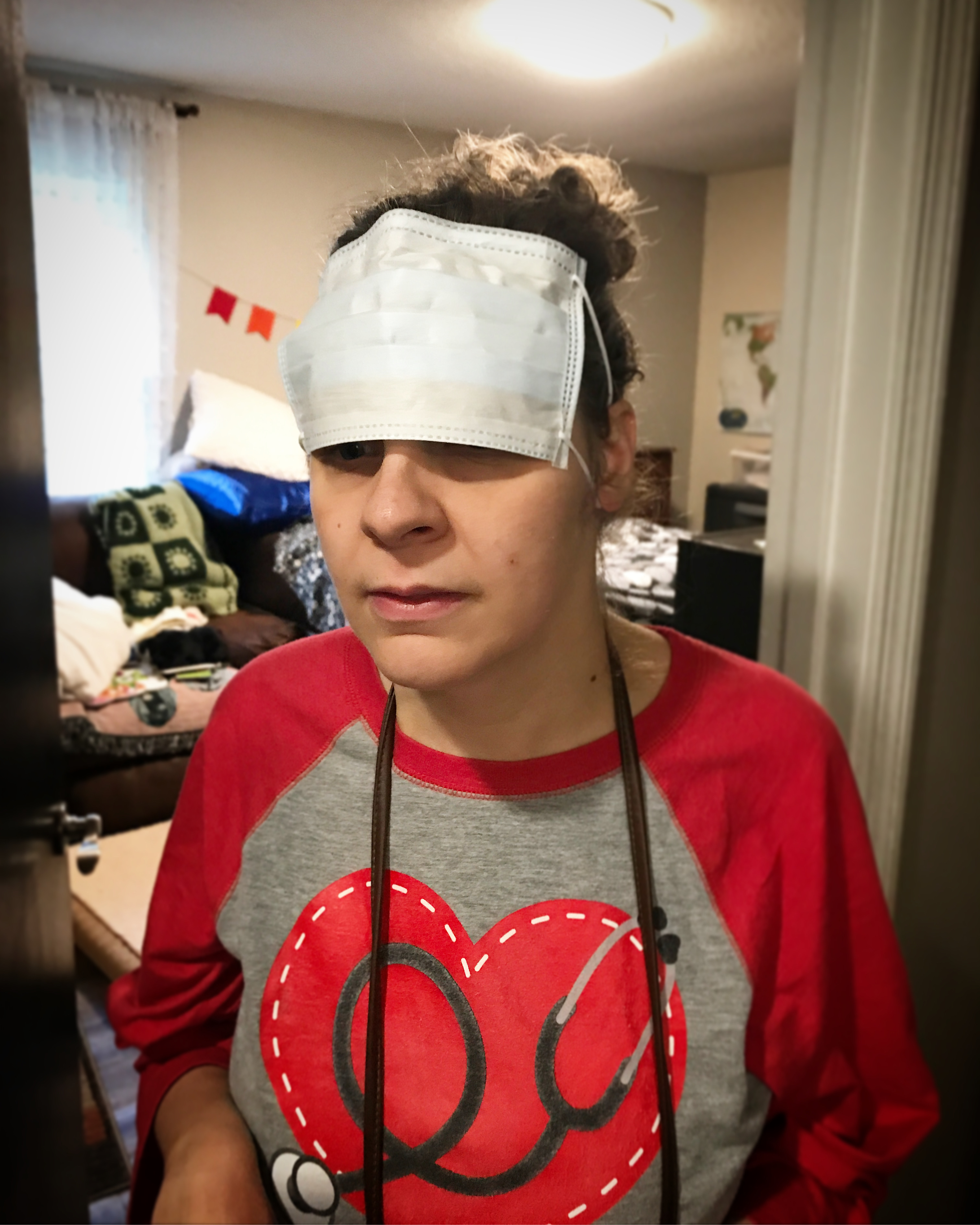 Jess is wearing a tee shirt with a picture of a stethoscope, and has on a medical mask that is covering her eyes and forehead.