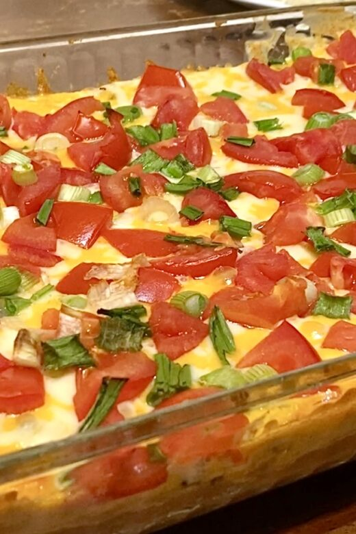 13x9 casserole dish with visible melted cheese, diced tomatoes, and sliced green onions