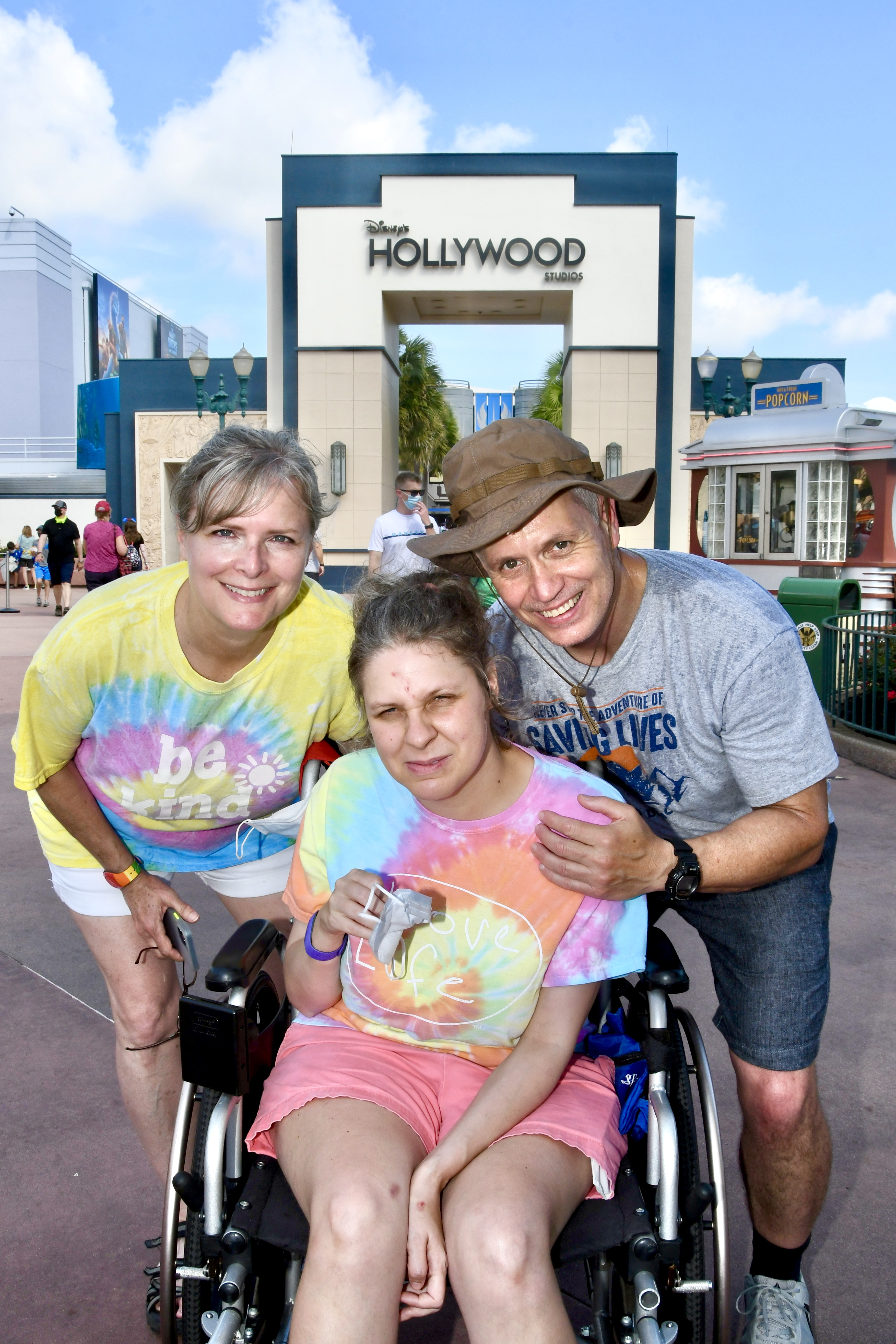 From Left to Right, Val, Jess, and Baddaddy. Jess is in her wheelchair, and Val and Baddaddy are leaning forward close to her. In the background behind them is the Hollywood Studios sign. The sky is mostly blue with a few white fluffy clouds.